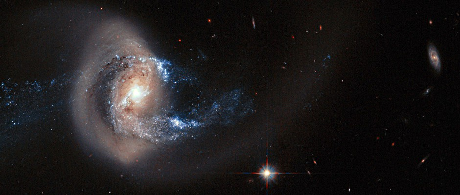 The NASA/ESA Hubble Space Telescope has captured this striking view of spiral galaxy NGC 7714. This galaxy has drifted too close to another nearby galaxy and the dramatic interaction has twisted its spiral arms out of shape, dragged streams of material out into space, and triggered bright bursts of star formation. Image credit: NASA/ESA