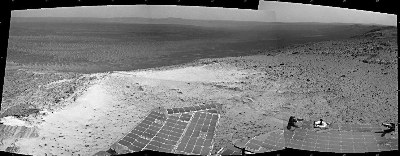 """NASA's Mars Exploration Rover Opportunity recorded this view just after reaching the summit of """"Cape Tribulation,"""" on the western rim of Endeavour Crater, on 6th January 2015, the 3,894th Martian day, or sol, of the rover's work on Mars. The site is about 440 feet (about 135 metres) higher in elevation than the plain surrounding the crater, higher than any other point Opportunity has reached since it began exploring the Endeavour rim in 2011. This view spans from northeast, at left, to south-southeast, at right. Image credit: NASA/JPL-Caltech"""