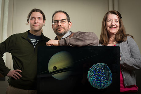 Graduate student James Stevenson, astronomer Jonathan Lunine and chemical engineer Paulette Clancy, with a Cassini image of Titan in the foreground of Saturn, and an azotosome, the theorised cell membrane on Titan. Image credit: Jason Koski/Cornell University Photography