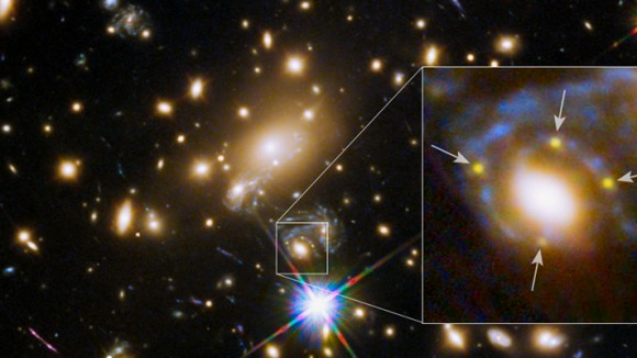 In this Hubble Space Telescope image, the many red galaxies are members of the massive MACS J1149.6+2223 cluster, which creates distorted and highly magnified images of the galaxies behind it. A large cluster galaxy (center of the box) has split the light from an exploding supernova in a magnified background galaxy into four yellow images (arrows) to form an Einstein Cross. Image credit: NASA, ESA, and S. Rodney (JHU) and the FrontierSN team; T. Treu (UCLA), P. Kelly (UC Berkeley) and the GLASS team; J. Lotz (STScI) and the Frontier Fields Team; M. Postman (STScI) and the CLASH team; and Z. Levay (STScI)