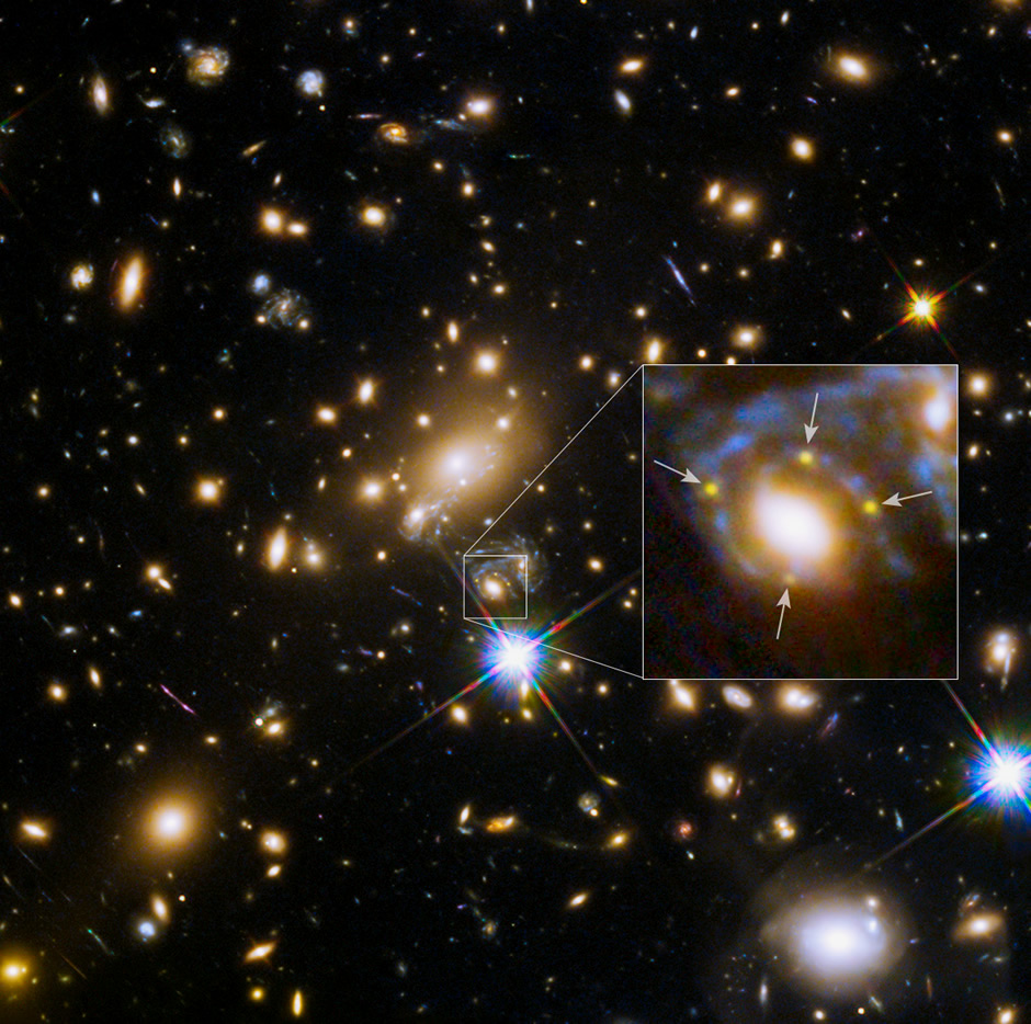 In this Hubble Space Telescope image, the many red galaxies are members of the massive MACSJ1149.6+2223 cluster, which creates distorted and highly magnified images of the galaxies behind it. A large cluster galaxy (center of the box) has split the light from an exploding supernova in a magnified background galaxy into four yellow images (arrows) to form an Einstein Cross. Image credit: NASA, ESA, and S. Rodney (JHU) and the FrontierSN team; T. Treu (UCLA), P. Kelly (UC Berkeley) and the GLASS team; J. Lotz (STScI) and the Frontier Fields Team; M. Postman (STScI) and the CLASH team; and Z. Levay (STScI)