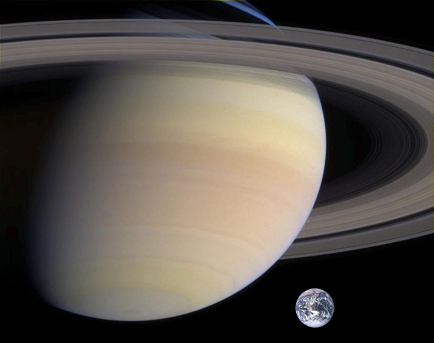 The relative sizes of Saturn and Earth compared, the ringed planet's globe is about nine times larger than our own. The magnificent ring system (seen in part here) has a diameter of around 170,000 miles (270,000 kilometres) — that is, 70% of the distance from the Earth to the Moon. Image credit: NASA, via Wikimedia Commons.