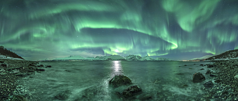 The vivid green Northern Lights dance above Lyngenfjord, the longest fjord in Troms county Norway, tracing out the shape of the Earth's magnetic field above the waters. The most common colour associated with aurorae, the green is produced by oxygen atoms and molecules energised by the impact of solar particles that have escaped the Sun's atmosphere, causing them to glow brightly. Image credit: © JanR.Olsen / RoyalMuseumsGreenwich.