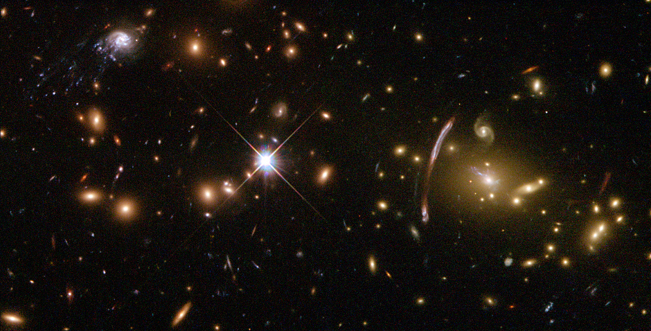 Abell2667 is a rich galaxy cluster some 3,000 million light-years away in the constellation Sculptor. The combined mass of all the member galaxies is so great that the cluster acts as a gravitational lens. Abel2667 shows a wide-ranging galaxy morphology in this image from the Hubble Space Telecope. Image credit: NASA, ESA, and J. Kneib (Laboratorie d'Astrophysique de Marseille).