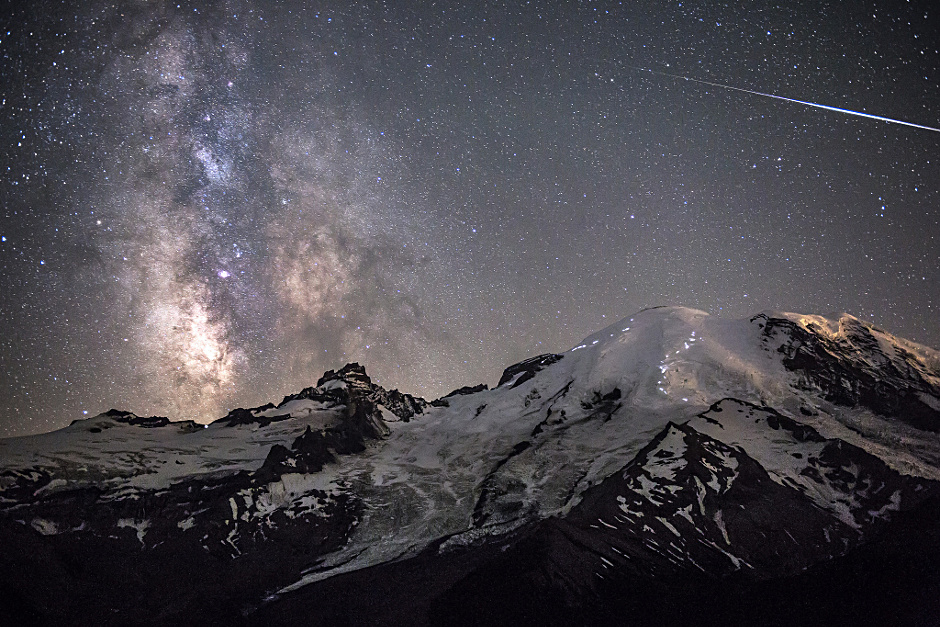 Following his first up-close encounter with a black bear, the photographer was relieved to reach his destination safely and capture this phenomenal image. A meteor can be seen piercing through the darkness as the MilkyWay towers above the 4,392-metre peak of MountRainier in Washington, USA. The white lights dotted across the rocky paths of the mountain's face are the headlamps of hikers ascending to the peak. Image credit: © BradGoldpaint /  RoyalMuseumsGreenwich. (Click image for full-size version.)
