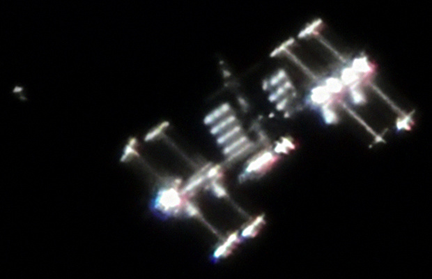 """The International Space Station photographed through a telescope by astrophotographer Ralf Vandebergh of the Netherlands. """"The image shows not only the ISS with very special lighting angle but also it shows activity around the ISS which is often the case. You see the Japanese Cargo Ship HTV-1 in its demonstration flight shortly before docking and just a few hundred metres below the ISS,"""" he said. Image credit: Ralf Vandebergh / Wikimedia Commons CC BY-SA 3.0."""