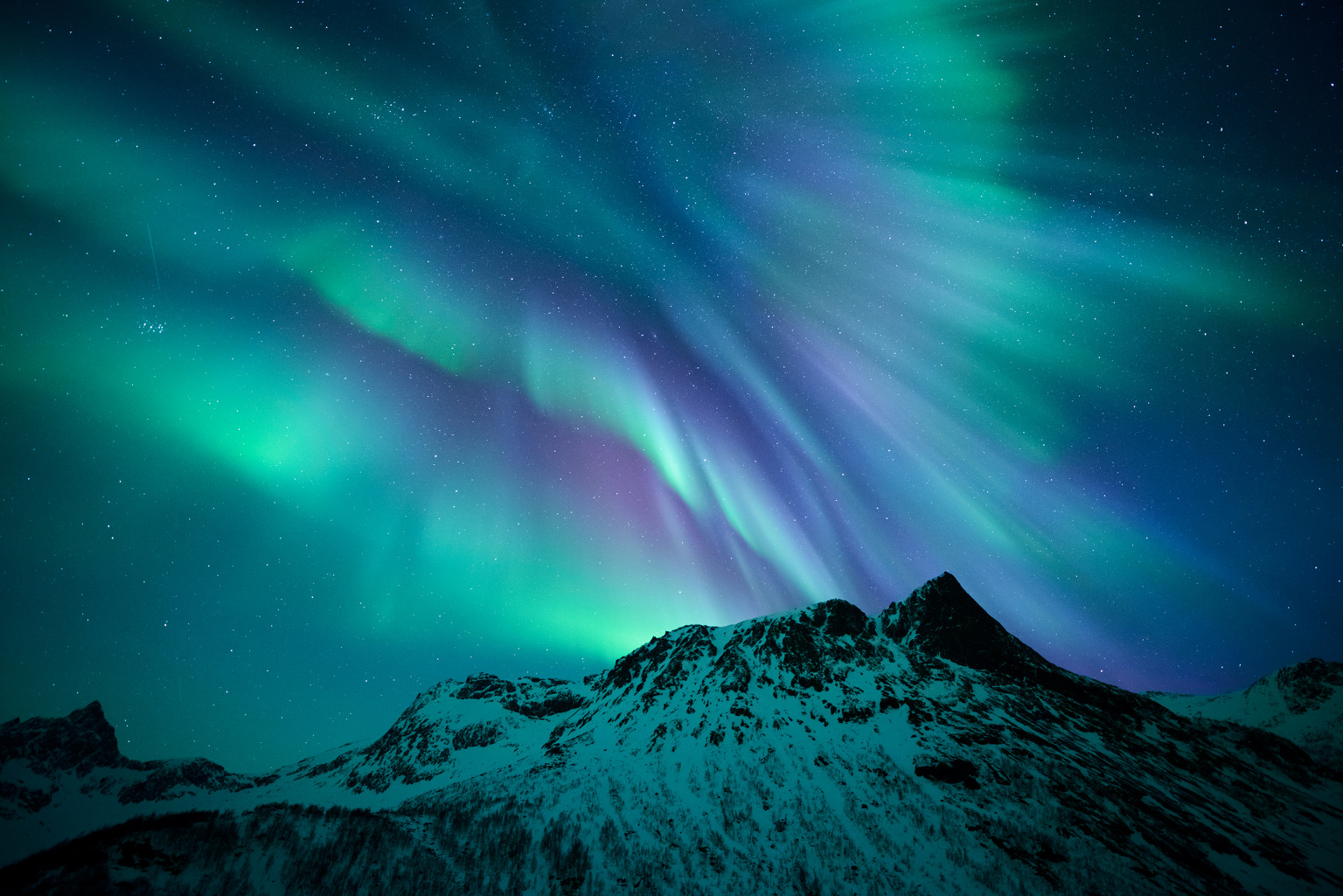 Motind is a hill in Troms. Living in Norway, the photographer has seen his fair share of aurorae, but on 21 January 2015 he witnessed the strongest variety of colours he had ever set eyes on in this beautiful explosion of purples and greens. Careening over the peaks of Senja, oxygen produces the greens and nitrogen the purples, seen in this particular display of the Northern Lights. Image credit: © RuneEngebo / RoyalMuseumsGreenwich. (Click image for full-size version.)
