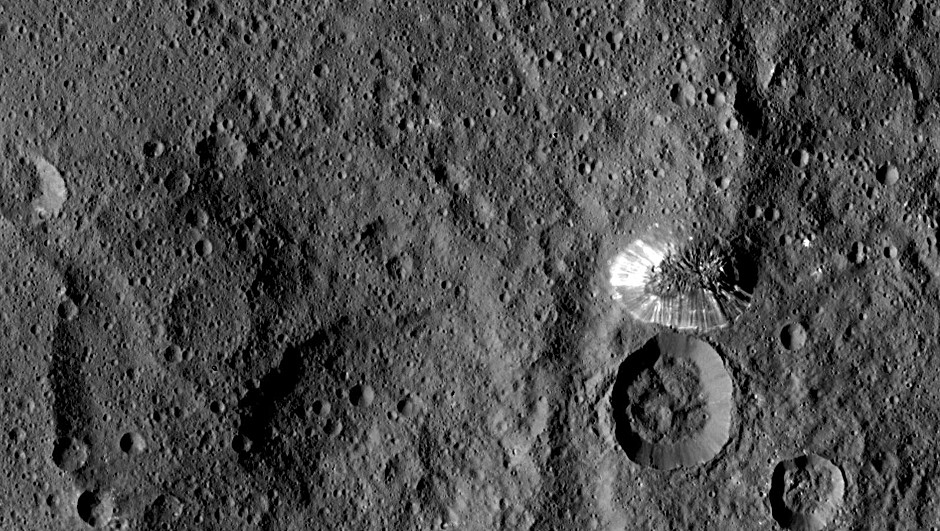 NASA's Dawn spacecraft spotted this tall, conical mountain on Ceres from a distance of 915 miles (1,470 kilometres). The mountain, located in the southern hemisphere, stands 4 miles (6 kilometres) high. Its perimeter is sharply defined, with almost no accumulated debris at the base of the brightly streaked slope with bright streaks. The image was taken on 19 August 2015 at a resolution of 450 feet (140 metres) per pixel. Image credit: NASA/JPL-Caltech/UCLA/MPS/DLR/IDA.