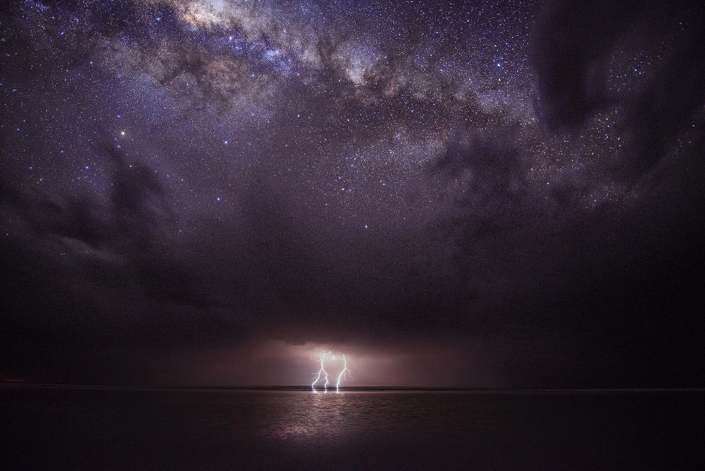 A phenomenal natural light show of a lightning storm emanating from the underside of ominous storm clouds juxtaposed with the gleaming stars of the MilkyWay above them. The photographer had watched the storm front over Kati-Thanda-Lake Eyre National Park in SouthAustralia for around two hours before capturing this tumultuous scene, using a graduated filter upside down to balance to exposure from top to bottom to showcase the beauty of our Galaxy. Image credit: © JulieFletcher / RoyalMuseumsGreenwich.