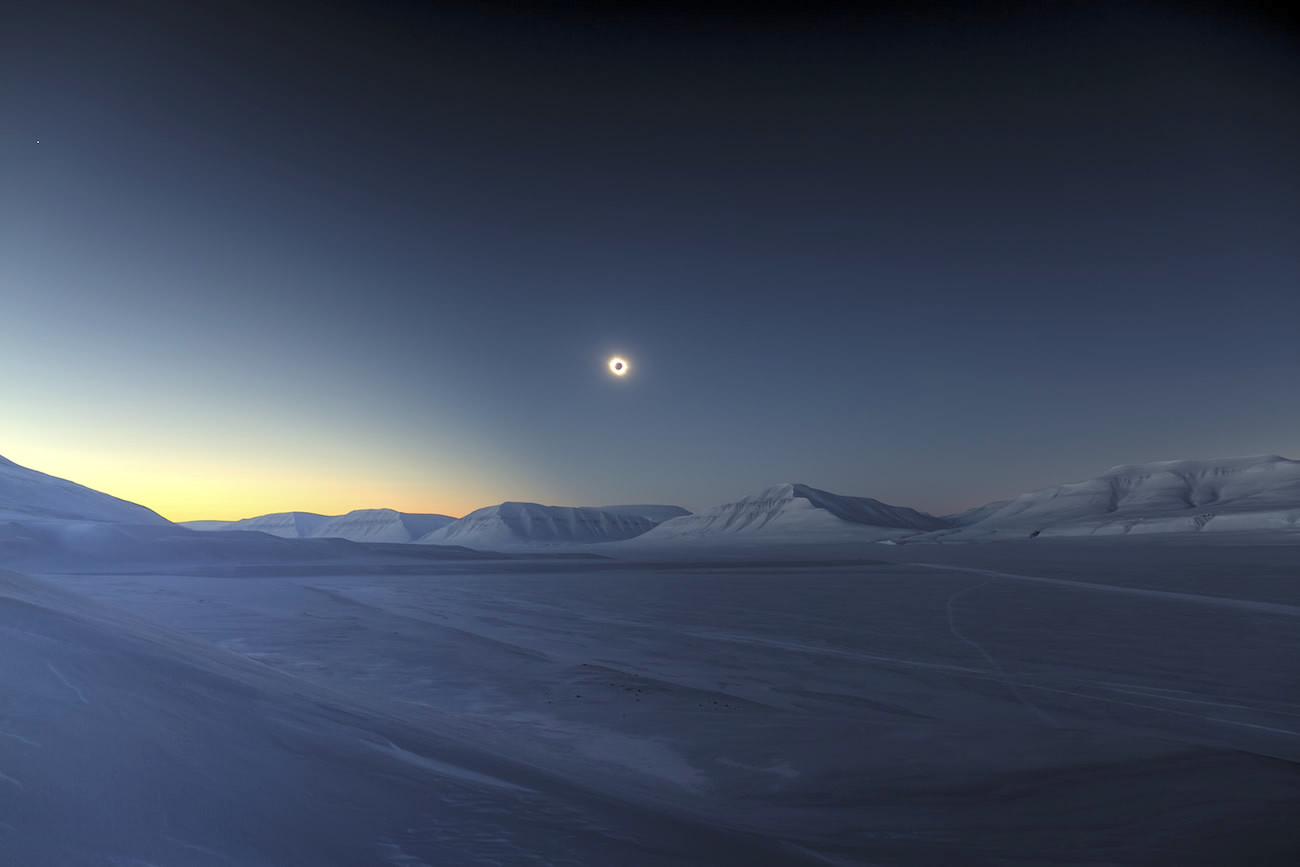 """What the photographer says: """"This is a picture of the 2015 solar eclipse as seen from Svalbard. Totality had begun 16seconds before this picture was taken, about 100metres above Sassendalen, Spitsbergen. The photo is an HDR [High Dynamic Range] composition made from three takes. We can see clearly the lunar shadow's edge in the sky. The bright spot in the upper left of the photo is Venus."""" Image credit: © LucJamet / RoyalMuseumsGreenwich."""