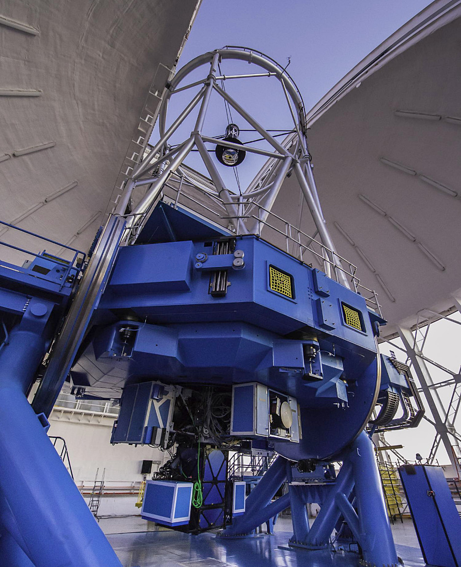 The Gemini Planet Imager on the Gemini South telescope. In the photo, GPI comprises the three box-like components attached to the telescope and hanging closest to the observatory floor. Other box-like components on the telescope are other instruments. Image credit: Manuel Paredes/Gemini Observatory/AURA.