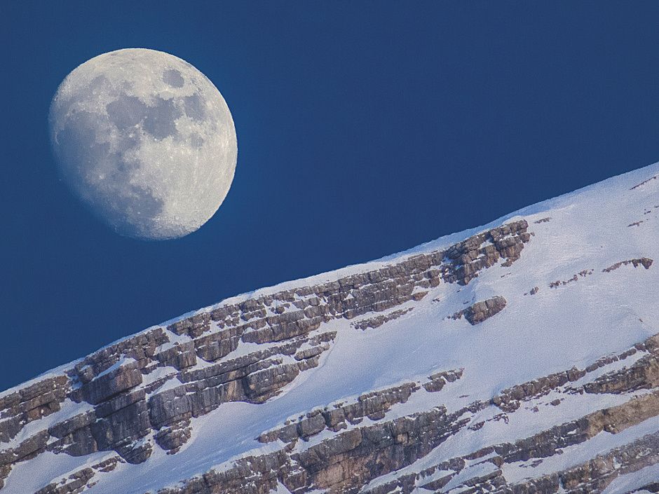 Late afternoon at San Vito di Cadore, Italy the Moon shines over Monte Antelao. The snow-covered dolomite ridge of the mountain and the Earth's only natural satellite bear a striking resemblance to one another, contrasting against the bright blue of the afternoon sky. The photographer noted the likeness of the image to a snowball bouncing down an inclined plane. Image credit: © MarcellaGiuliaPace / RoyalMuseumsGreenwich.