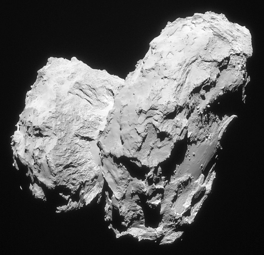 Two comets collided at low speed in the early solar system to give rise to the distinctive 'rubber duck' shape of Comet 67P/Churyumov–Gerasimenko. The image shown here was taken on 22 August 2014 at a distance of 63.4 kilometres (39.4 miles) from the comet's centre. It shows the comet's small lobe to the left, with the striking cliffs of Hathor clearly visible. In the foreground on the far right, the smooth Imhotep region can be seen on the large lobe. The image scale is 5.4 metres/pixel and it measures 5.5 kilometres (3.4 miles) across. Image credit: ESA/Rosetta/Navcam — CCBY-SAIGO3.0.