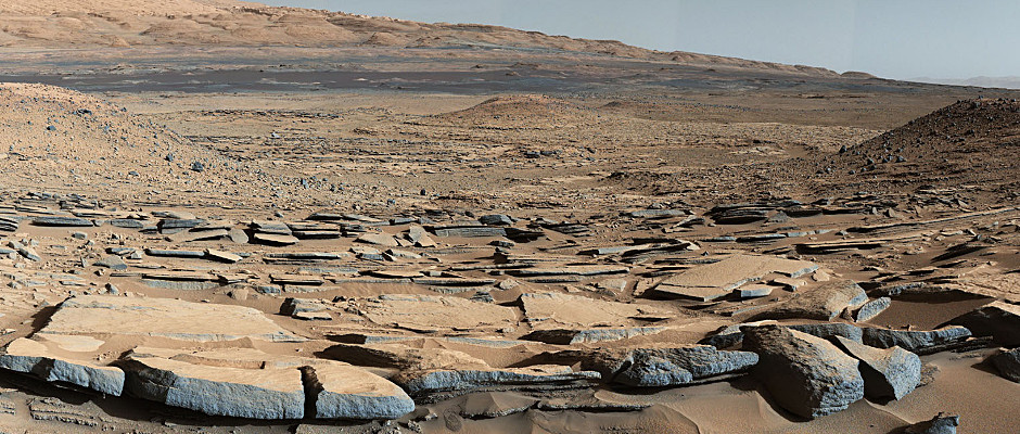 """A view from the """"Kimberley"""" formation on Mars taken by NASA's Curiosity rover. The strata in the foreground dip towards the base of MountSharp, indicating flow of water toward a basin that existed before the larger bulk of the mountain formed. The colours are adjusted so that rocks look approximately as they would if they were on Earth, to help geologists interpret the rocks. This """"white balancing"""" to adjust for the lighting on Mars overly compensates for the absence of blue on the planet, making the sky appear light blue and sometimes giving dark, black rocks a blue cast. This image was taken by the Mast Camera (Mastcam) on Curiosity on the 580th Martian day, or sol, of the mission. Image credit: NASA/JPL-Caltech/MSSS."""