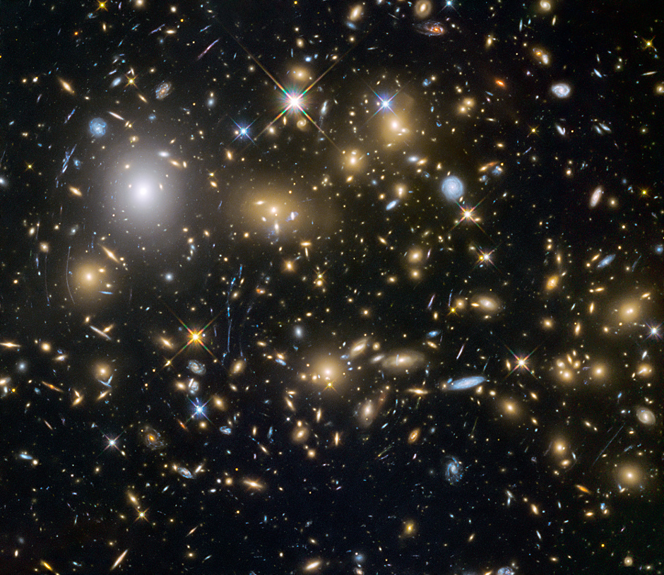 This image from the NASA/ESA Hubble Space Telescope shows the galaxy cluster MACSJ0717.5+3745. It is one of the most massive galaxy clusters known, and it is also the largest known gravitational lens. Of all of the galaxy clusters known and measured, MACS J0717 lenses the largest area of the sky. Image credit: NASA, ESA and the HST Frontier Fields team (STScI).