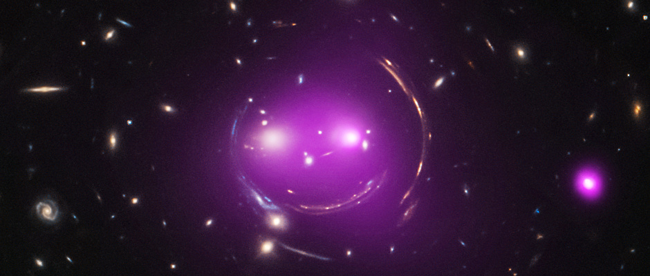 """The latest results from the """"Cheshire Cat"""" group of galaxies 4.6billion light-years away in the constellation Ursa Major show how manifestations of Einstein's 100-year-old Theory of General Relativity can lead to new discoveries today. Astronomers have given the group this name because of its resemblance to the smiling feline from Alice's Adventures in Wonderland. This composite image shows individual galaxies of the system, as well as the gravitationally lensed arcs, seen in optical light from NASA's Hubble Space Telescope, in addition to X-rays from NASA's Chandra X-ray Observatory (pink). Image credits: X-ray: NASA/CXC/UA/J.Irwin et al; Optical: NASA/STScI."""