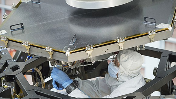 An engineer at NASA's Goddard Space Flight Center in Greenbelt, Maryland, works to install the first of 18 flight mirrors onto the James Webb Space Telescope's backplane structure. Image credits: NASA/Chris Gunn.