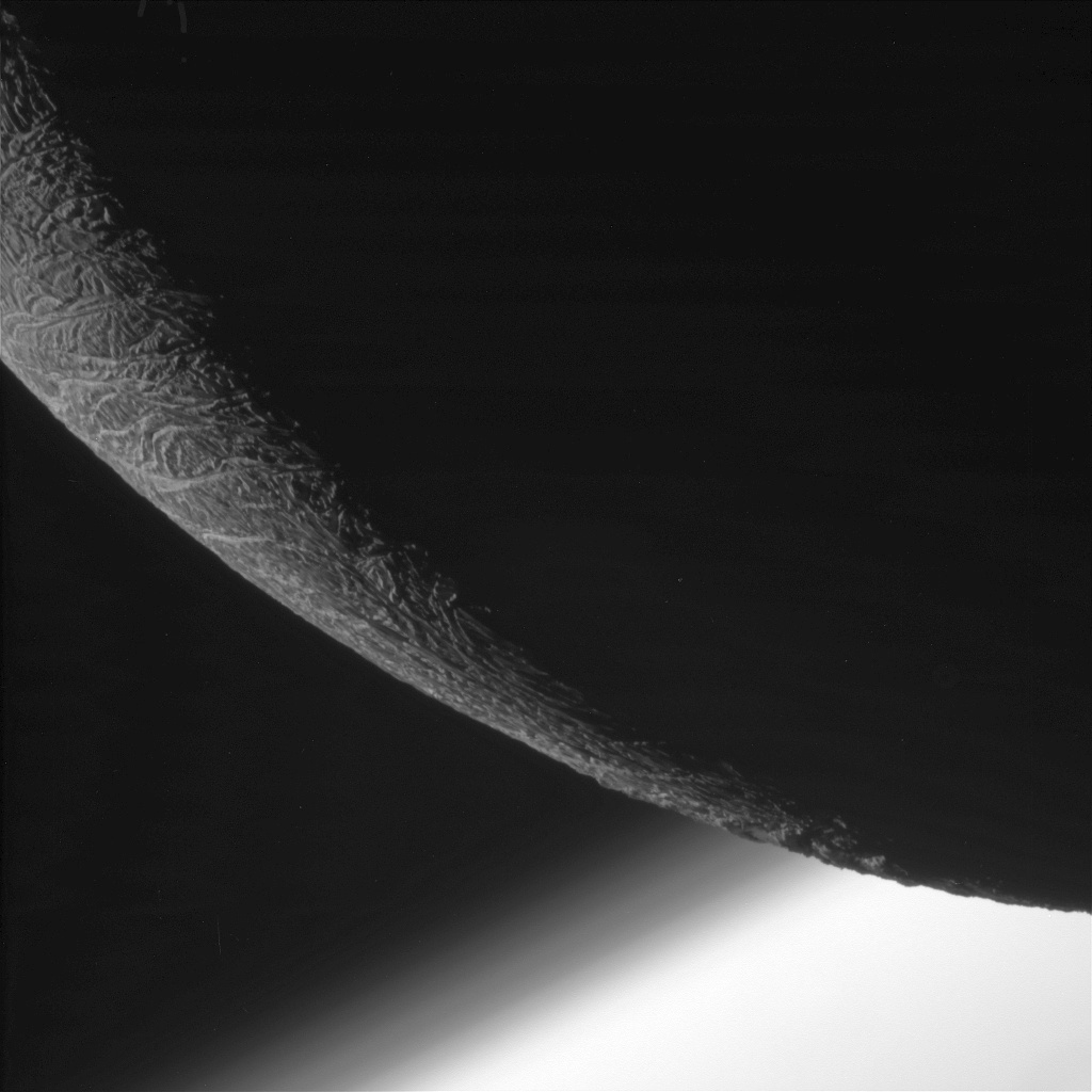 NASA's Cassini spacecraft paused during its final close flyby of Enceladus to focus on the icy moon's craggy, dimly lit limb, with the planet Saturn beyond. Layers can be seen in the high hazes of Saturn's upper atmosphere, in the gradient that separates the planet from space. North on Enceladus is up and rotated 27 degrees to the left. The image was taken with the Cassini spacecraft narrow-angle camera on 19 December 2015, using a spectral filter, which preferentially admits wavelengths of near-infrared light. The view was acquired at a distance of approximately 15,000 miles (24,000 kilometres) from Enceladus. Image scale is 479 feet (146 metres) per pixel. Image credit: NASA/JPL-Caltech/Space Science Institute.