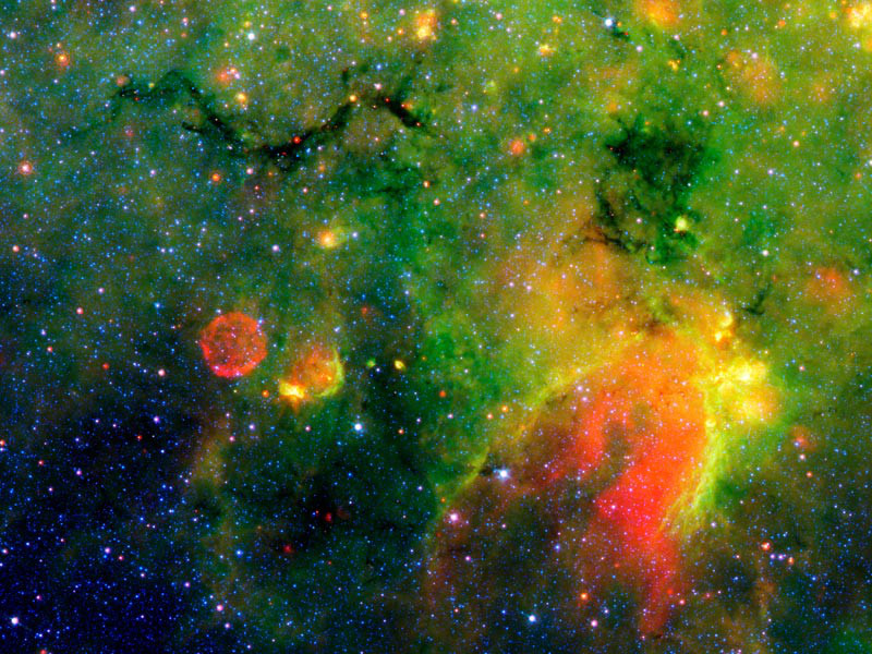 A false-colour, infrared image of a dark cloud as seen against the bright background of Milky Way emission. Within the snake-like cloud structure seen here, dust and gas are congealing into new stars that are detected as embedded, hot cores. Observations with the Submillimetre Array find that these hot cores are often rich in organic chemicals. Image credit: NASA/JPL-Caltech.