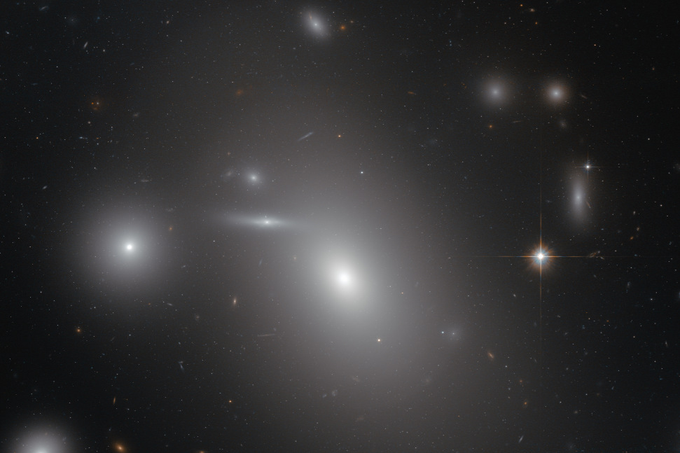 This image shows the elliptical galaxy NGC4889 in front of hundreds of background galaxies, and deeply embedded within the Coma galaxy cluster. Well-hidden from human eyes, there is a gigantic supermassive black hole at the centre of the galaxy. Image credit: NASA & ESA.