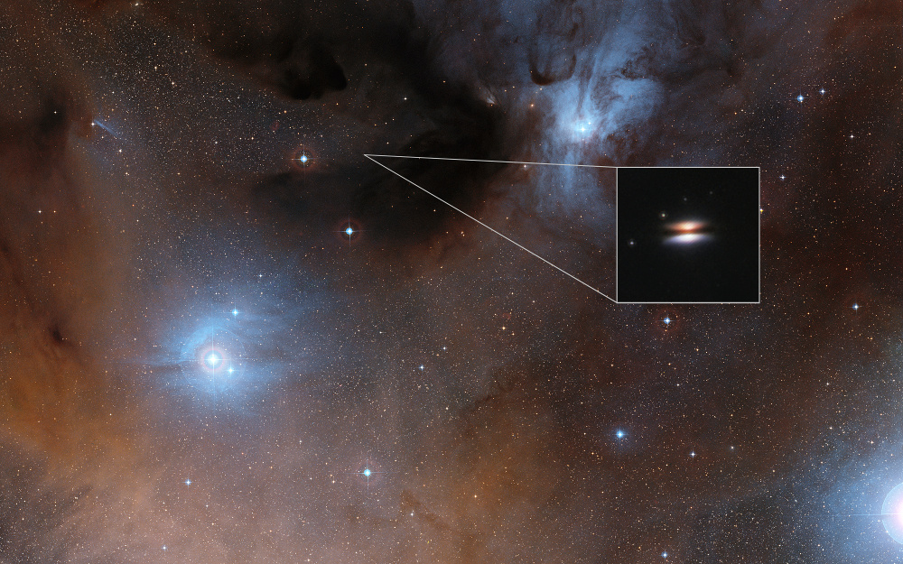 The young star 2MASSJ16281370-2431391 lies in the spectacular RhoOphiuchi star formation region, about 400 light-years from Earth. It is surrounded by a disc of gas and dust — such discs are called protoplanetary discs as they are the early stages in the creation of planetary systems. This particular disc is seen nearly edge-on, and its appearance in visible light pictures has led to its being nicknamed the Flying Saucer. The main image shows part of the Rho Ophiuchi region and a much enlarged close-up infrared view of the Flying Saucer from the NASA/ESA Hubble Space Telescope is shown as an insert. Image credit: Digitised Sky Survey 2/NASA/ESA.