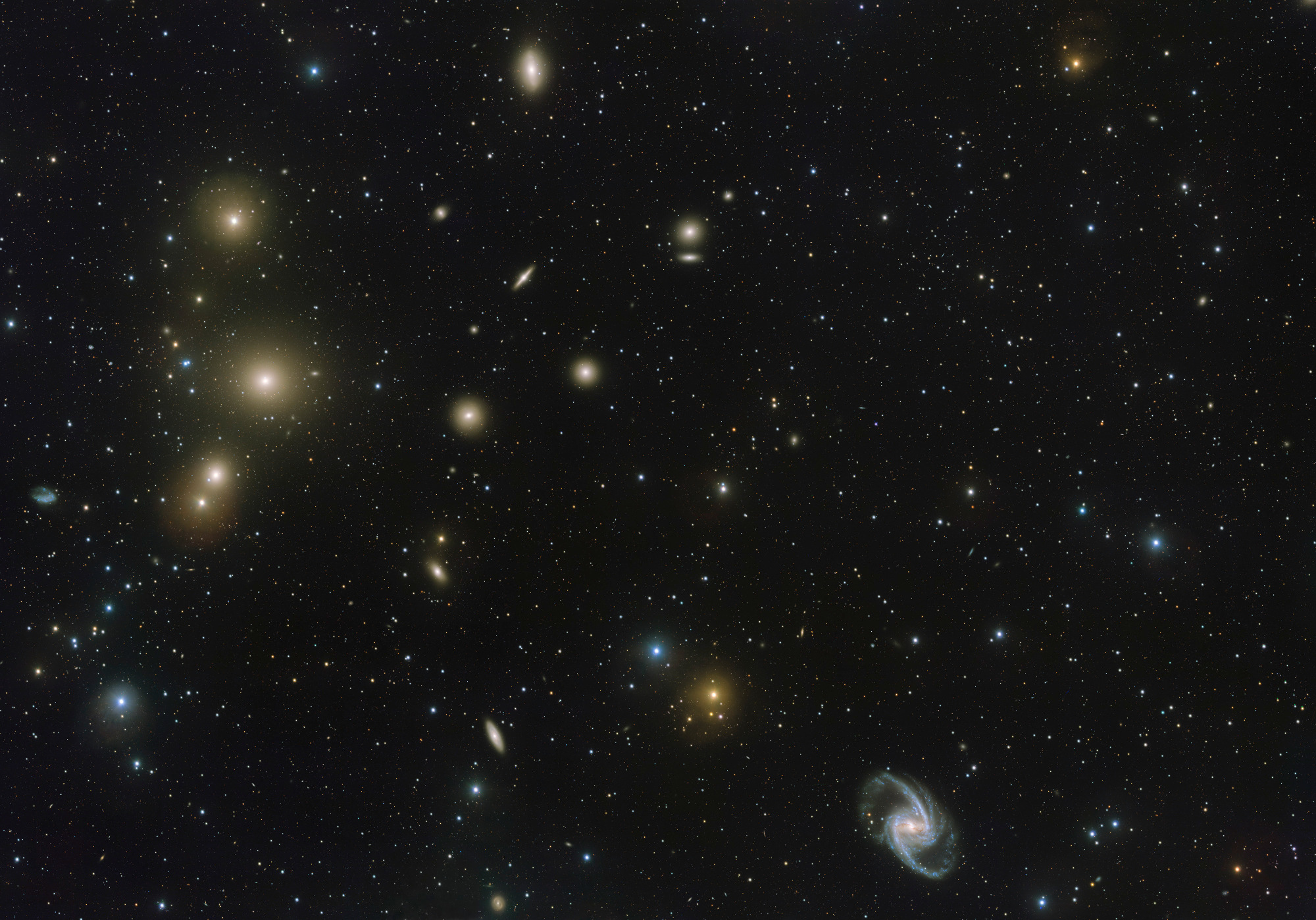 The Fornax Galaxy Cluster is one of the closest of such groupings beyond our Local Group of galaxies. This new VLT Survey Telescope image shows the central part of the cluster in great detail. At the lower-right is the elegant barred-spiral galaxy NGC1365 and to the left the big elliptical NGC1399. Click the image for a full-size version. Image credit: ESO. Acknowledgement: Aniello Grado and Luca Limatola.