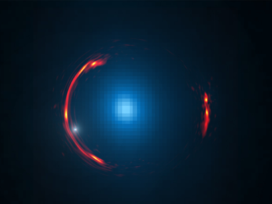 Composite image of the gravitational lens SDP.81 showing the distorted ALMA image of the more distant galaxy (red arcs) and the Hubble optical image of the nearby lensing galaxy (blue centre object). By analysing the distortions in the ring, astronomers have determined that a dark dwarf galaxy (data indicated by white dot near left lower arc segment) is lurking nearly 4billion light-years away. Image credit: Y. Hezaveh, Stanford Univ.; ALMA (NRAO/ESO/NAOJ); NASA/ESA Hubble Space Telescope.
