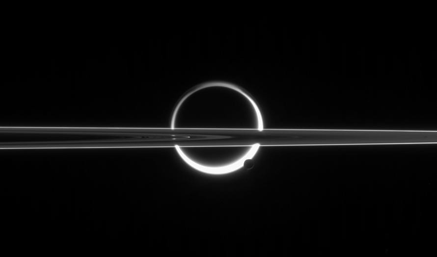 In this image from the NASA/ESA Cassini spacecraft, Saturn's largest moon — Titan — appears to be speared by the planet's almost edge-on rings, while smaller moon Enceladus lies superimposed on Titan's crescent. Click the image for a larger version. Image credit: NASA/JPL/Space Science Institute.