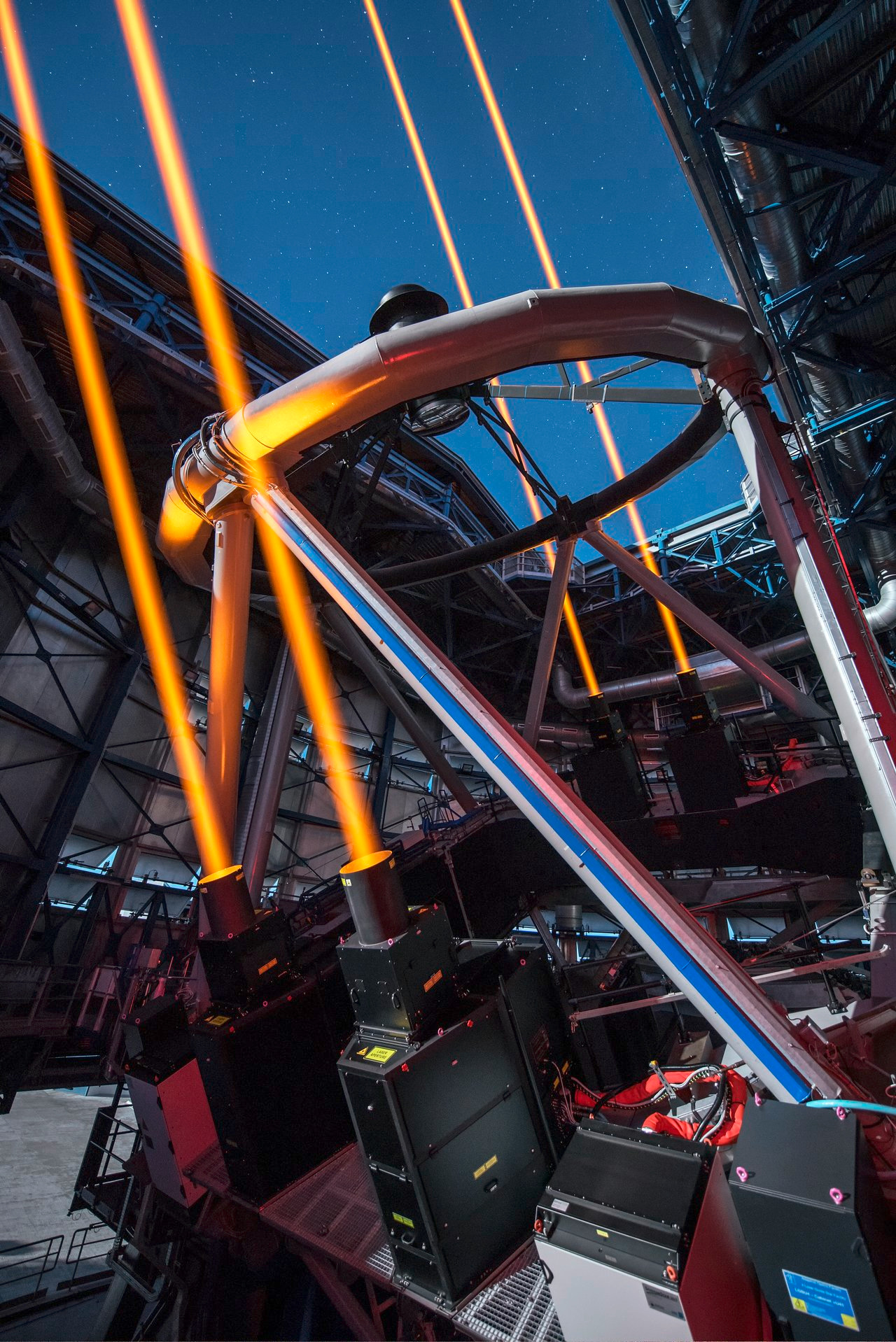 This image shows the four 30-centimetre diameter, 22-watt beams emerging from the new 589nm laser system on Unit Telescope 4 of the VLT. Image credit: ESO/G. Hüdepohl.