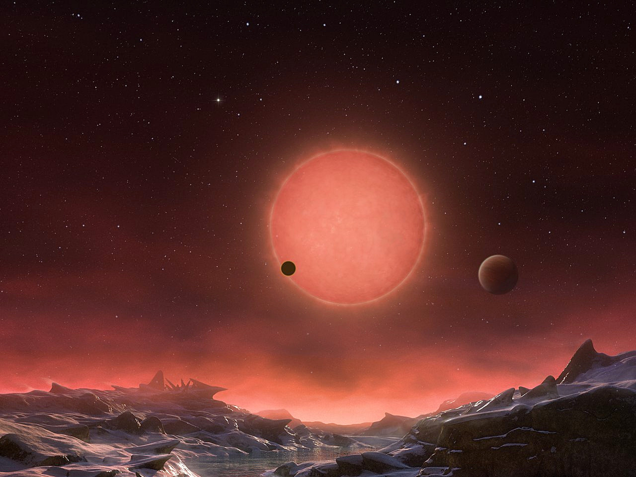 This artist's impression shows an imagined view from the surface one of the three planets orbiting an ultra-cool dwarf star just 40 light-years from Earth that were discovered using the TRAPPIST telescope at ESO's La Silla Observatory. These worlds have sizes and temperatures similar to those of Venus and Earth and are the best targets found so far for the search for life outside the solar system. They are the first planets ever discovered around such a tiny and dim star. In this view, one of the inner planets is seen in transit across the disc of its tiny and dim parent star. Image credit: ESO/M. Kornmesser.