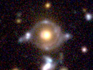 Eye of Horus in pseudo colour. The enlarged image to the right (field of view of 23 arcseconds x 19 arcseconds) show two arcs/rings with different colours. The inner arc has a reddish hue, while the outer arc has a blue tint. These arcs are lensed images of the two background galaxies. There are blobs in and around the arcs/rings, which are also the lensed images of those background galaxies. The yellow-ish object at the centre is a massive galaxy at z = 0.79 (distance 7 billion light-years), which bends the light from the two background galaxies. Image credit: NAOJ.