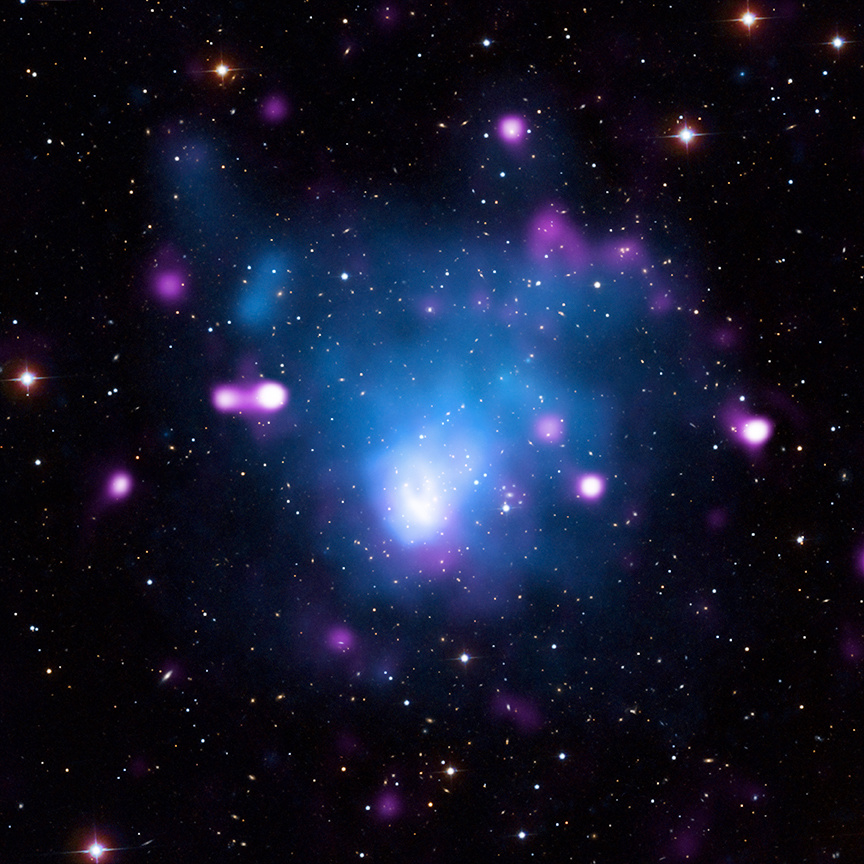 Merging galaxy clusters can generate enormous shock waves, similar to cold fronts in weather on Earth. This system, known as Abell665 in the constellation of Ursa Major, has an extremely powerful shockwave, second only to the famous Bullet Cluster. Here, X-rays from Chandra (blue) show hot gas in the cluster, which lies about 2.2billion light-years from Earth. The bow wave shape of the shock is shown by the large white region near the centre of the image. The Chandra image has been added to radio emission (purple) and visible light data from the Sloan Digital Sky Survey showing galaxies and stars (white). Image credit: X-ray: NASA/CXC/Univ. of Alabama/S.Dasadia et al; Radio: NSF/NRAO/VLA; Optical: SDSS.
