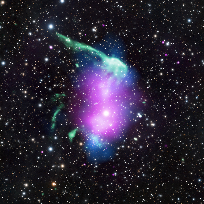 """The phenomenon of pareidolia is when people see familiar shapes in images. This galaxy cluster, which is known as RXJ0603.3+4214, has invoked the nickname of the """"Toothbrush Cluster"""" because of its resemblance to the dental tool. In fact, the stem of the brush is due to radio waves (green) while the diffuse emission where the toothpaste would go is produced by X-rays observed by Chandra (purple). Visible light data from the Subaru telescope show galaxies and stars (white) and a map from gravitational lensing (blue) shows the concentration of the mass, which is mostly (about 80precent) dark matter. RXJ0603.3+4214 lies about 2.7billion light-years away in the constellation of Auriga. Image credit: X-ray: NASA/CXC/SAO/R. van Weeren et al; Radio: NCRA/TIFR/GMRT; Optical: NAOJ/Subaru."""