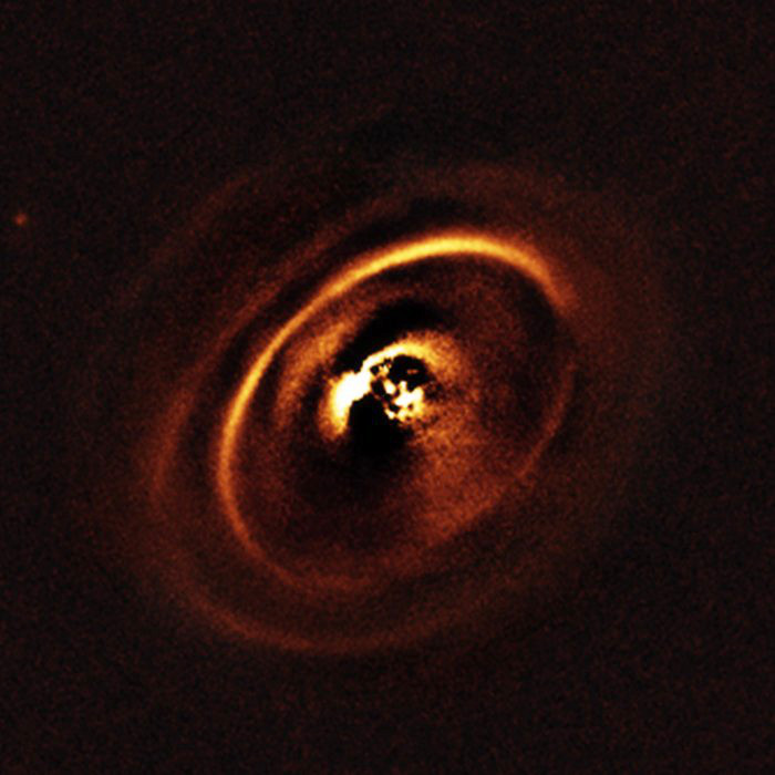 Using the ESO's SPHERE instrument at the Very Large Telescope, a team of astronomers observed the planetary disc surrounding the star RXJ1615 which lies in the constellation of Scorpius, 600 light-years from Earth. The observations show a complex system of concentric rings surrounding the young star, forming a shape resembling a titanic version of the rings that encircle Saturn. Such an intricate sculpting of rings in a protoplanetary disc has only been imaged a handful of times before. Image credit: ESO, J. de Boer et al.