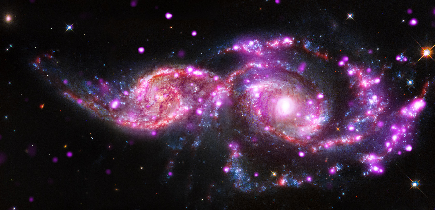 NGC 2207 and IC 2163 in the constellation of Ursa Major are galaxies in the act of a grazing collision. This new composite image of the system contains X-rays from Chandra (pink) along with optical (blue, white, orange and brown) plus infrared data (red). Image credit: X-ray: NASA/CXC/SAO/S.Mineo et al, Optical: NASA/STScI, Infrared: NASA/JPL-Caltech