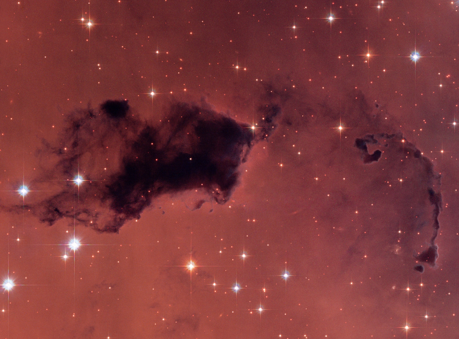 "This Hubble image features dark knots of gas and dust known as ""Bok globules,"" which are dense pockets in larger molecular clouds. Similar islands of material in the early universe could have held as much water vapour as we find in our galaxy today, despite containing a thousand times less oxygen. Image credit: NASA, ESA, and The Hubble Heritage Team"