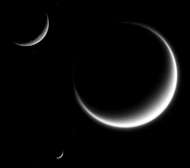 This image from NASA's Cassini spacecraft shows three moons — Rhea (top), Titan and Mimas (bottom). Titan appears fuzzy because we only see its cloud layers and light refracts within its atmosphere, extending the crescent. Image credit: NASA/JPL-Caltech/Space Science Institute.
