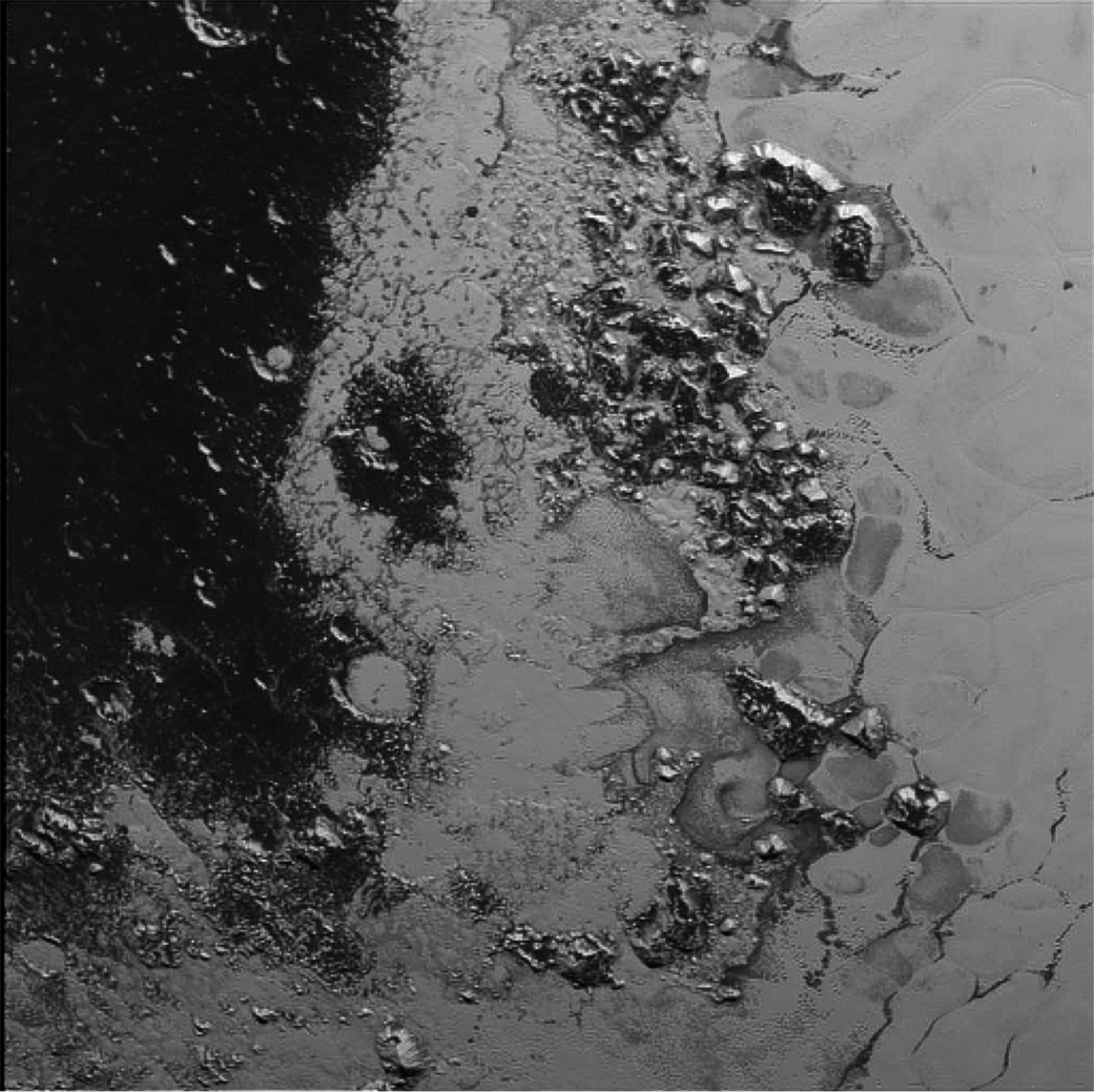 A newly discovered mountain range lies near the southwestern margin of Pluto's Tombaugh Regio (Tombaugh Region), situated between bright, icy plains and dark, heavily-cratered terrain. This image was acquired by New Horizons' Long Range Reconnaissance Imager (LORRI) on July 14, 2015 from a distance of 48,000 miles (77,000 kilometers) and sent back to Earth on July 20. Features as small as a half-mile (1 kilometer) across are visible. Credit: NASA/JHUAPL/SWRI