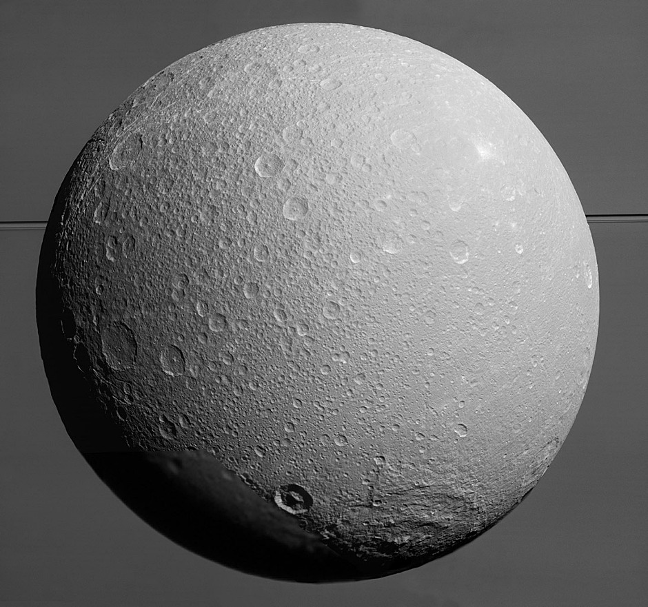 This view from NASA's Cassini spacecraft looks toward Saturn's icy moon Dione, with giant Saturn and its rings in the background, just prior to the mission's final close approach to the moon on 17 August 2015. At lower right is the large, multi-ringed impact basin named Evander, which is about 220 miles (350 kilometres) wide. The canyons of Padua Chasma, features that form part of Dione's bright, wispy terrain, reach into the darkness at left. Image credit: NASA/JPL-Caltech/Space Science Institute.
