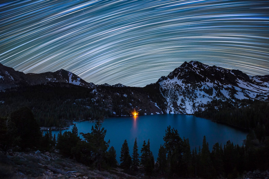 Star trails illuminate the night sky over a campfire-lit Green Lake in the Hoover Wilderness of California. Star trails are a popular subject for astrophotographers to capture using long-exposure times. Whilst they appear to illustrate the movement of the stars, they are in fact depicting the rotation of the Earth on its axis. Image credit: © Dan Barr / Royal Museums Greenwich. (Click image for full-size version.)