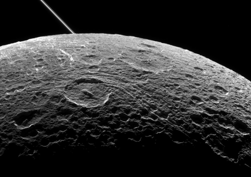 A view of Saturn's moon Dione captured by NASA's Cassini spacecraft during a close flyby on 16 June 2015. The diagonal line near upper left is the rings of Saturn, in the distance. Image credit: NASA/JPL-Caltech/Space Science Institute.