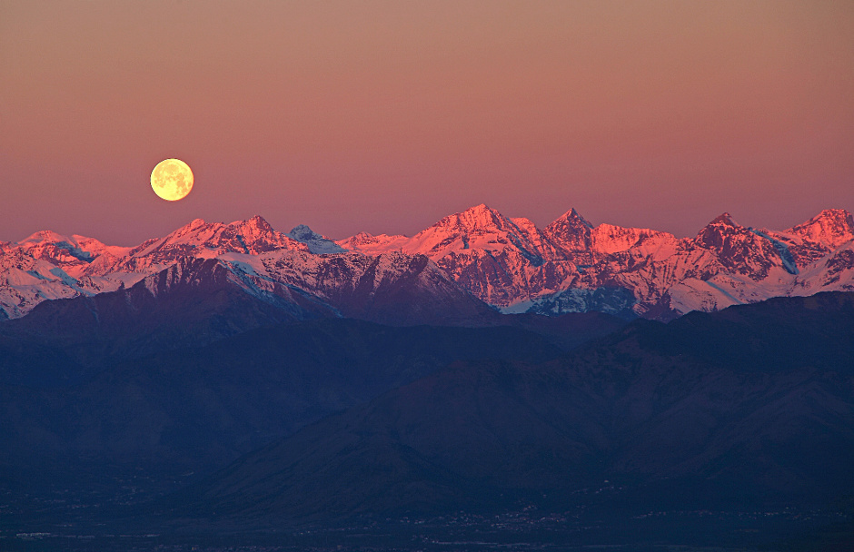 The majestic sight of the fullMoon setting behind the rose-tinted Alps. Taken in the silent surroundings of Supergahill in Turin, Italy, mere minutes before sunrise. Image credit: © StefanoDeRosa /  RoyalMuseumsGreenwich.