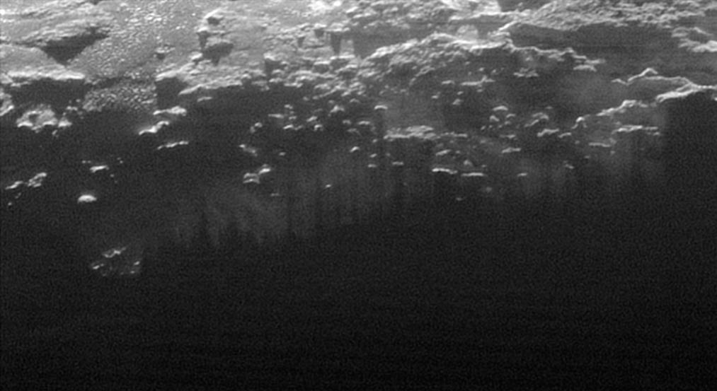 In this small section of the larger crescent image of Pluto, taken by NASA's New Horizons just 15 minutes after the spacecraft's closest approach on July 14, 2015, the setting sun illuminates a fog or near-surface haze, which is cut by the parallel shadows of many local hills and small mountains. The image was taken from a distance of 11,000 miles (18,000 kilometers), and the width of the image is 115 miles (185 kilometers). Credit: NASA/Johns Hopkins University Applied Physics Laboratory/Southwest Research Institute