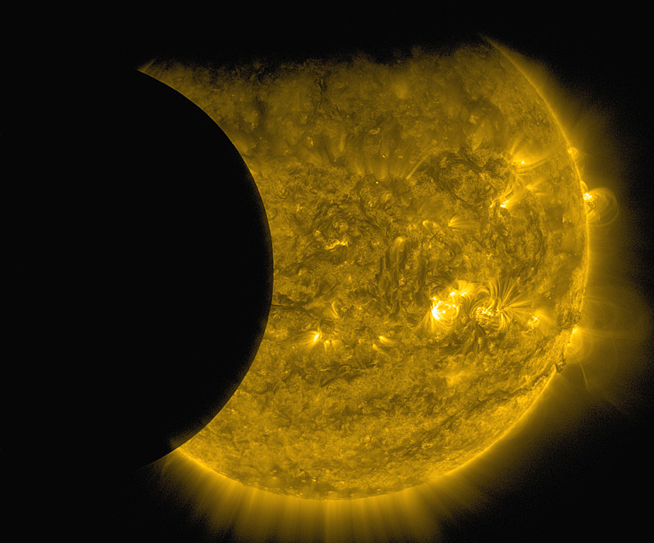 NASA's Solar Dynamics Observatory captured this image of Earth and the Moon transiting the Sun together on 13 September 2015. The edge of Earth, visible near the top of the frame, appears fuzzy because Earth's atmosphere blocks different amounts of light at different altitudes. On the left, the Moon's edge is perfectly crisp, because it has no atmosphere. This image was taken in extreme ultraviolet wavelengths of 171 angstroms. Though this light is invisible to our eyes, it is typically colourised in gold. Image credits: NASA/SDO.