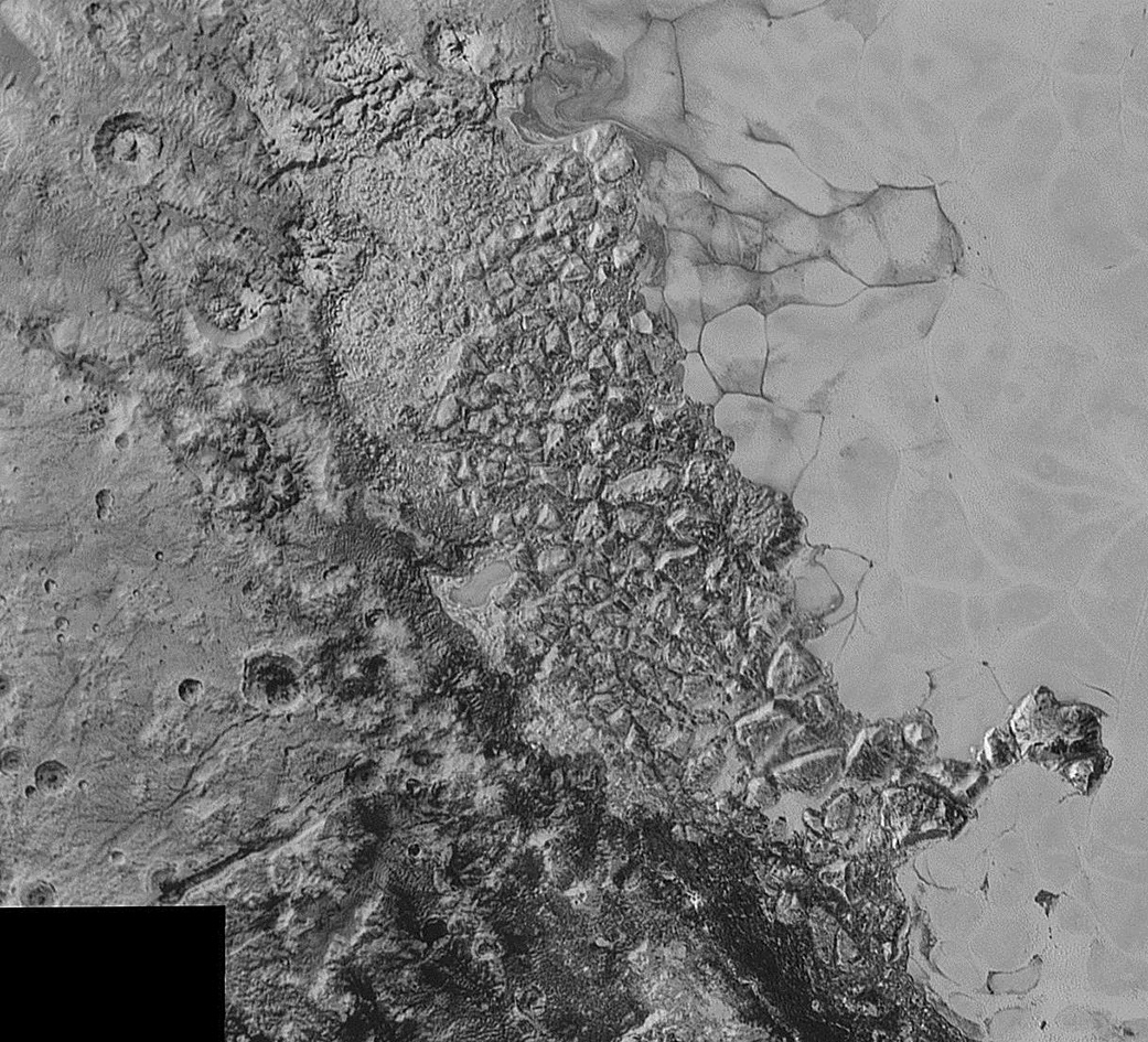 In the centre of this 300-mile (470-kilometre) wide image of Pluto from NASA's New Horizons spacecraft is a large region of jumbled, broken terrain on the northwestern edge of the vast, icy plain informally called Sputnik Planum, to the right. The smallest visible features are 0.5 miles (0.8 kilometres) in size. This image was taken as New Horizons flew past Pluto on 14 July 2015, from a distance of 50,000 miles (80,000 kilometres). Image credits: NASA/Johns Hopkins University Applied Physics Laboratory/Southwest Research Institute.