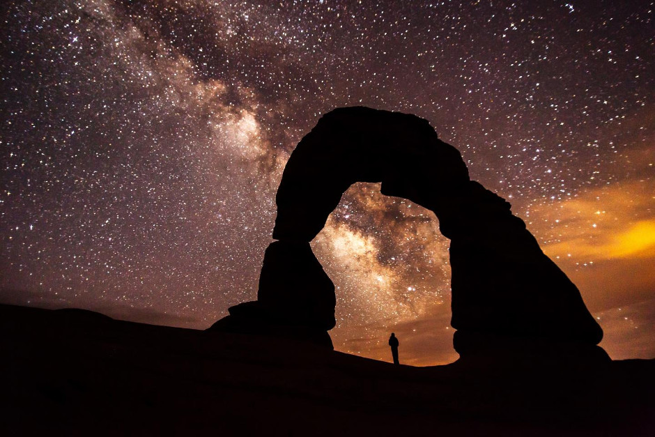 A solitary figure contemplates the cosmos under Delicate Arch in the Arches National Park, Utah, USA. A new study shows National Park visitors highly value the nighttime sky and want park managers to minimise light pollution. Light from urban centres can travel as far as 250 miles. Image credit: National Park Service.