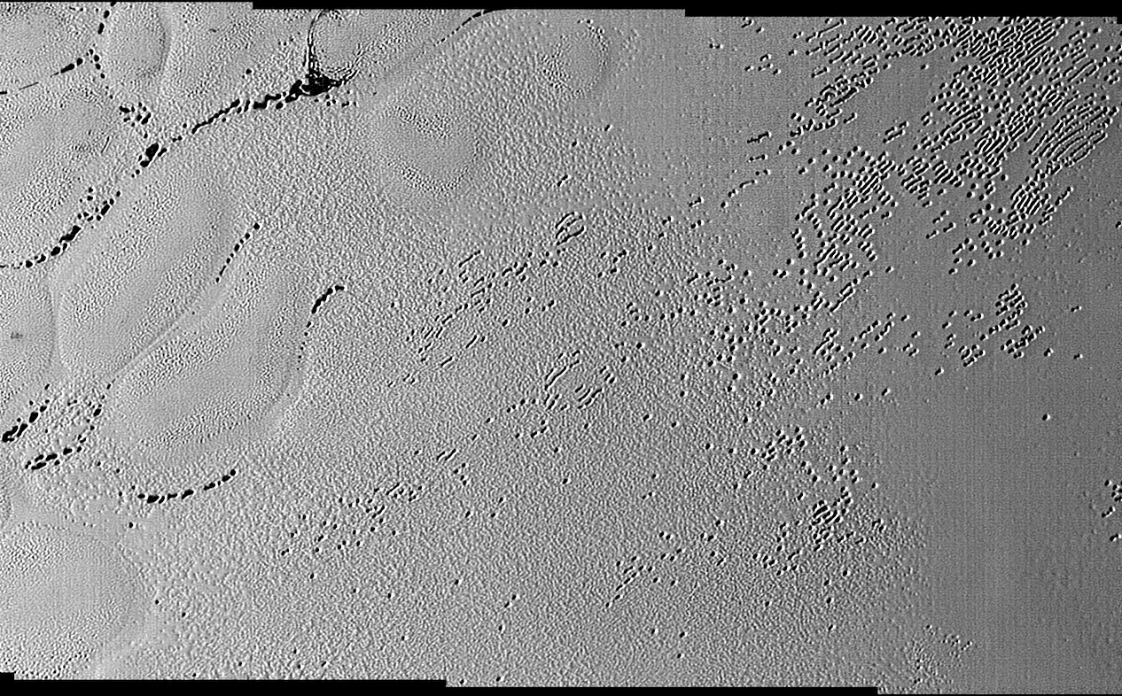 This image was taken by the Long Range Reconnaissance Imager (LORRI) on NASA's New Horizons spacecraft shortly before closest approach to Pluto on 14 July 2015; it resolves details as small as 270 yards (250 metres). The scene shown is about 130 miles (210 kilometres) across. The Sun illuminates the scene from the left, and north is to the upper left. Image credits: NASA/JHUAPL/SwRI.