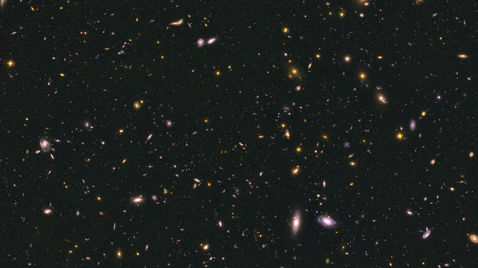 This image shows a region of the Cosmic Assembly Near-infrared Deep Extragalactic Legacy Survey (CANDELS) GOODS-South field, which is one of the fields used in this study. This image combines data taken from the Hubble Space Telescope's optical and near-infrared cameras, and contains galaxies at a range of distances. The larger galaxies are relatively close by, while the smallest specks hail from the earlier universe.  Some of the smallest dots in this image are those used in this study; their light is coming from 0.5 to 1.5 billion years after the Big Bang. Image credit: NASA, ESA, A. Koekemoer and the CANDELS science team.