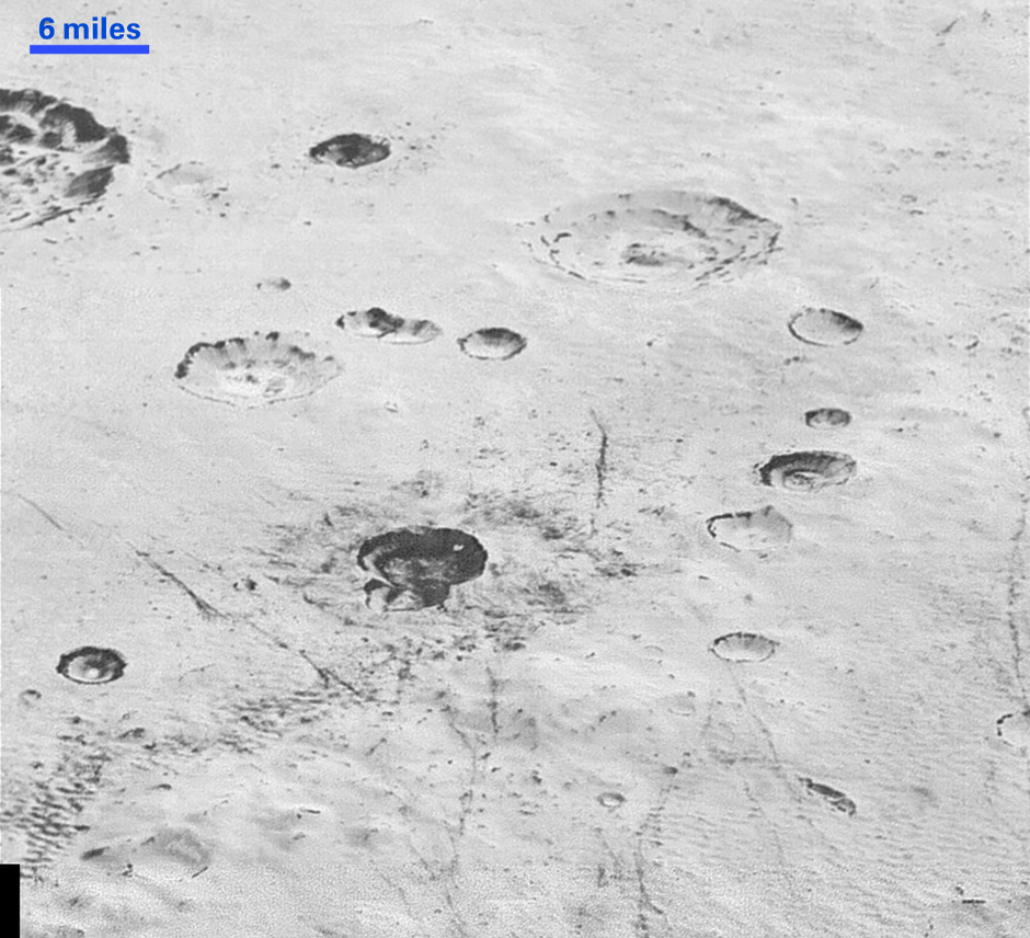 """This highest-resolution image from NASA's New Horizons spacecraft reveals new details of Pluto's rugged, icy cratered plains. Notice the layering in the interior walls of many craters (the large crater at upper right is a good example). Layers in geology usually mean an important change in composition or event, but at the moment New Horizons team members do not know if they are seeing local, regional or global layering. The darker crater in the lower center is apparently younger than the others, because dark material ejected from within — its """"ejecta blanket"""" — has not been erased and can still be made out. The origin of the many dark linear features trending roughly vertically in the bottom half of the image is under debate, but may be tectonic. Most of the craters seen here lie within the 155-mile (250-kilometre)-wide Burney Basin, whose outer rim or ring forms the line of hills or low mountains at bottom. The basin is informally named after Venetia Burney, the English schoolgirl who first proposed the name """"Pluto"""" for the newly discovered planet in 1930. The top of the image is to Pluto's northwest. Image credit: NASA/JHUAPL/SwRI."""