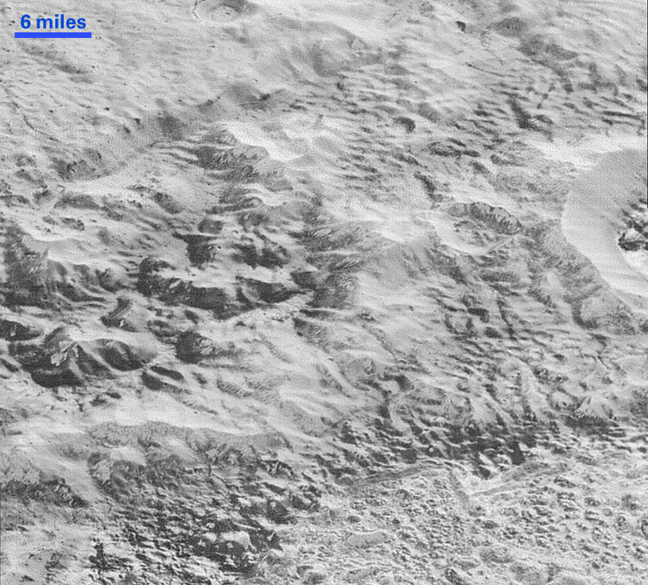 This highest-resolution image from NASA's New Horizons spacecraft shows how erosion and faulting has sculpted this portion of Pluto's icy crust into rugged badlands. The prominent 1.2-mile-high cliff at the top, running from left to upper right, is part of a great canyon system that stretches for hundreds of miles across Pluto's northern hemisphere. New Horizons team members think that the mountains in the middle are made of water ice, but have been modified by the movement of nitrogen or other exotic ice glaciers over long periods of time, resulting in a muted landscape of rounded peaks and intervening sets of short ridges. At the bottom of this 50-mile-wide image, the terrain transforms dramatically into a fractured and finely broken up floor at the northwest margin of the giant ice plain informally called Sputnik Planum. The top of the image is to Pluto's northwest. Image credit: NASA/JHUAPL/SwRI.